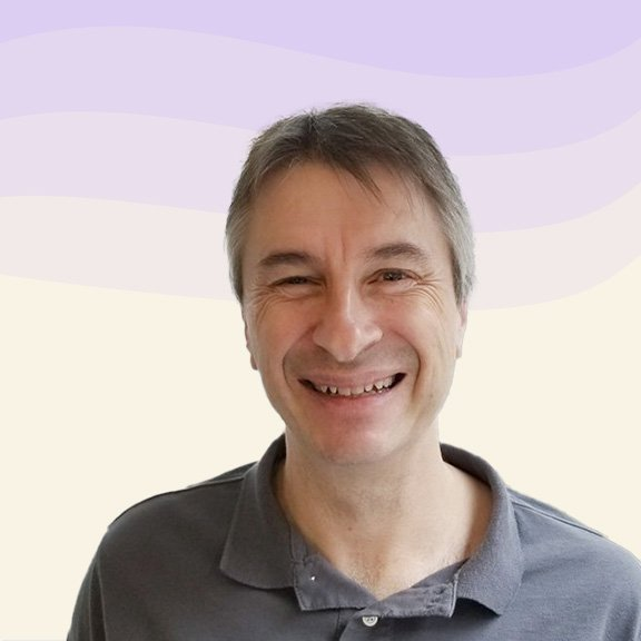 Portrait of Michael smiling, who has medium-length greying hair and is wearing a grey-blue polo shirt.