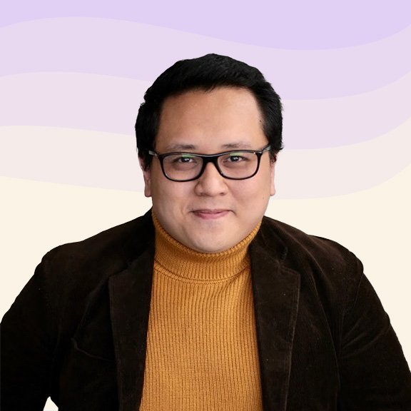 Portrait of Sam smiling softly, who has short black hair and glasses and is wearing a mustard-colored turtleneck sweater and sport coat