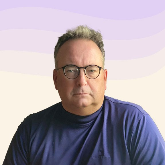 Portrait of Ted looking serious, who has short grey hair and round glasses wearing a purple sweatshirt.